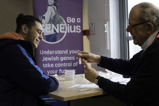 Jnetics_Screening advisor explaining to school student how the saliva kit works at GENEius school screening event